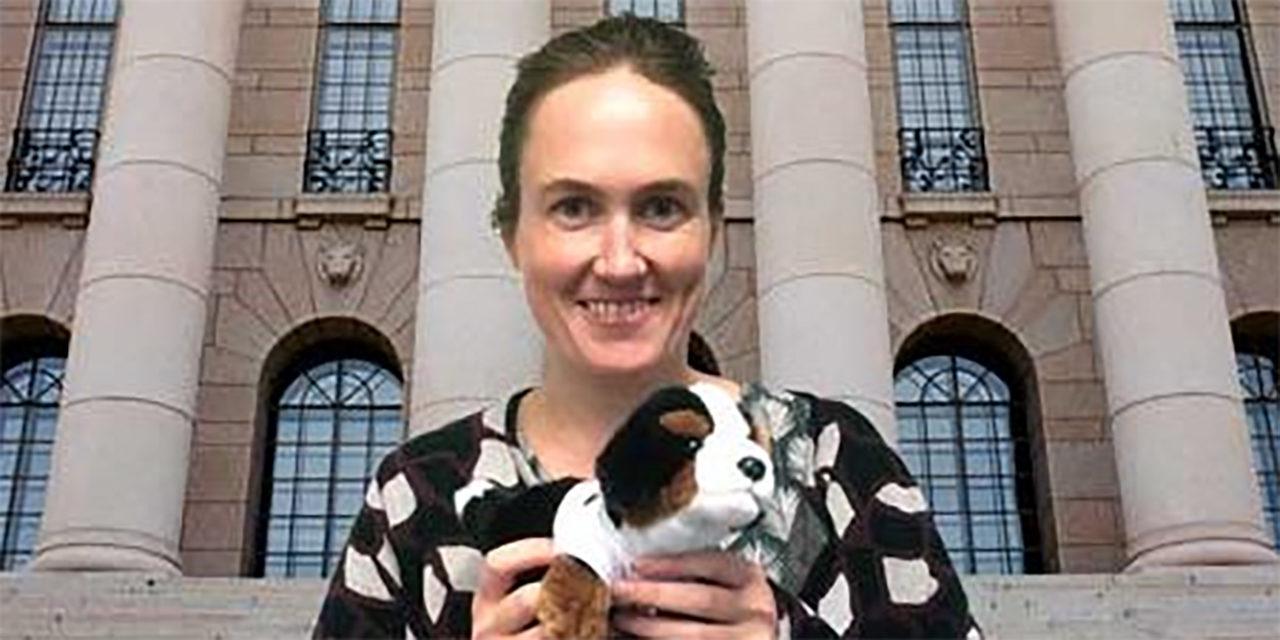 SEYn toiminnanjohtaja Kati Pulli pitää pehmolelukoiraa kädessään. Taustalla näkyvät eduskuntatalon pylväät