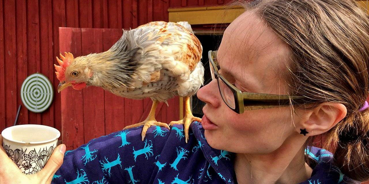 Kuvassa nainen pitää kahvikuppia kädessään, kana olkapäällä keikkuen