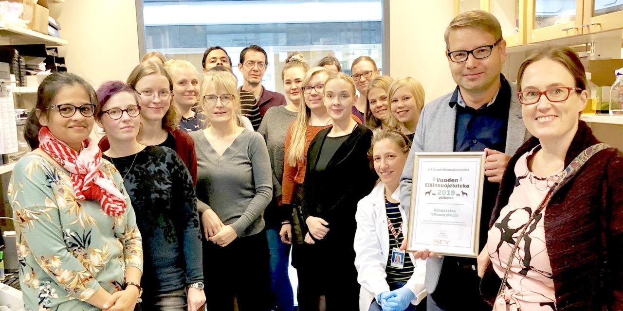 Professori Hannes Lohi pitää Vuoden eläinsuojeluteko -diplomia. Vieressä SEYn toiminnanjohtaja Kati Pulli ja Lohen tutkimusryhmään kuuluvia tutkijoita