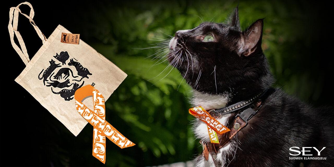 Mustavalkoinen kissa katsoo ylöspäin. Kaulassaan sillä on oranssi kissanauha. Mustalla taustalla lisäksi kuva kissanauhasta ja kissakangaskassista.