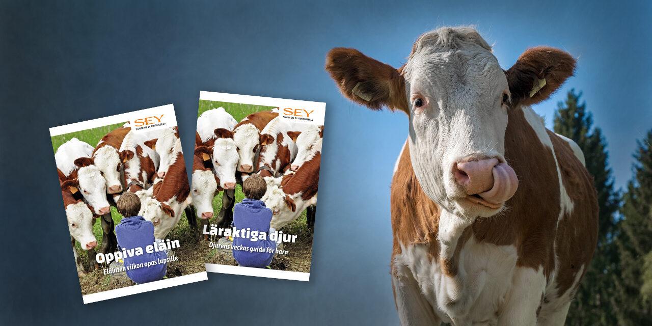 Kuvassa lehmä sekä SEYn vuoden 2021 lasten oppaan suomen- ja ruotsinkieliset kannet