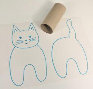 Kuvassa on piirretty pahville erikseen kissan etuosa (pää,vartalon etuosa ja jalat) sekä takaosa (häntä, takaosa, jalat). Kuvassa on myös vessapaperirulla lähellä pahvia.