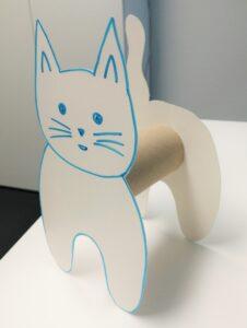 Kuvassa on valmis askartelun tuotos. Keskellä on vessapaperirulla, jonka toiseen päähän on liimattu pahvista leikattu kissan etuosa ja toiseen takaosa.